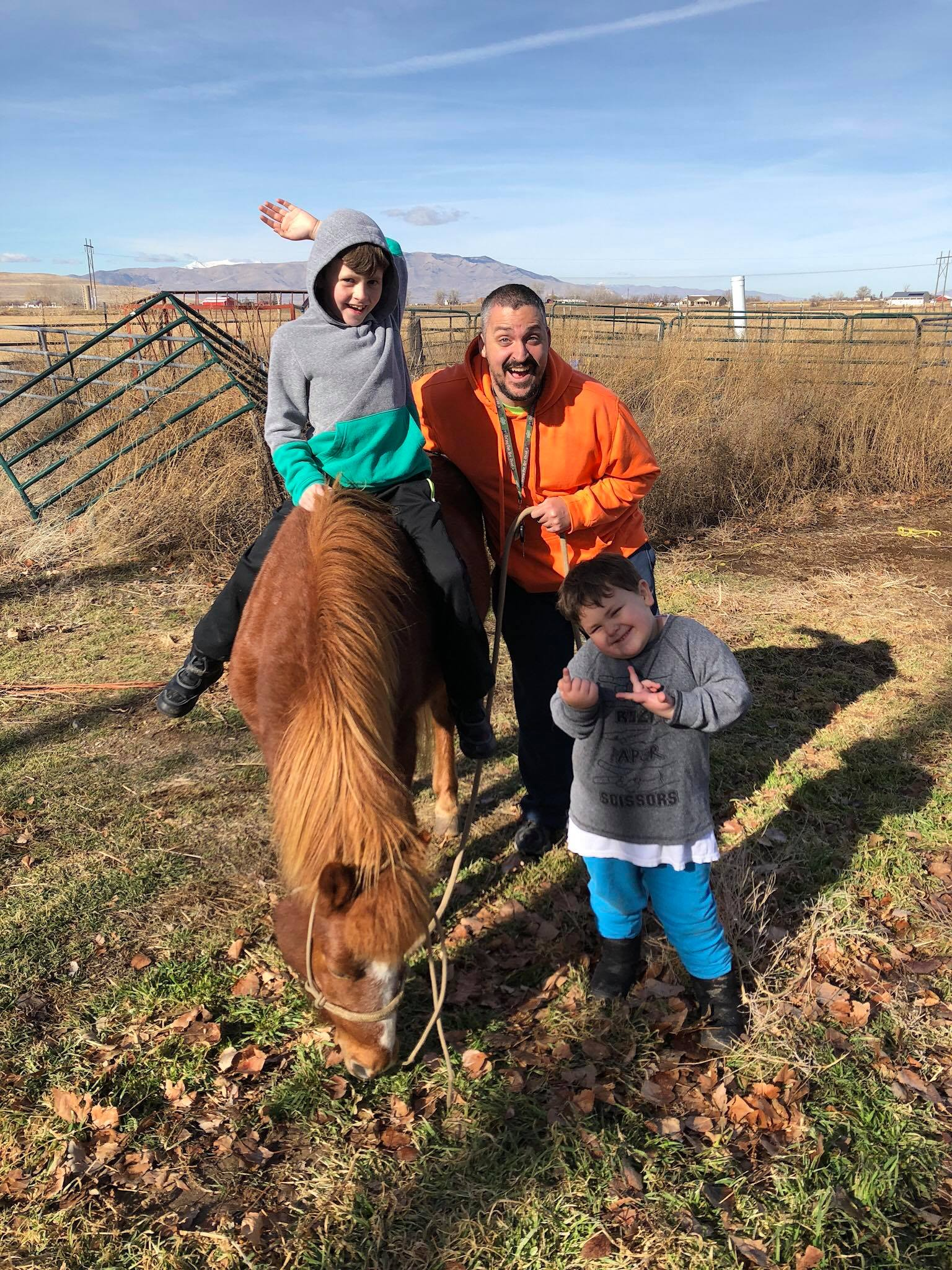 A  9 Year old boy sitting on a pony while his dad and brother hang out nearby
