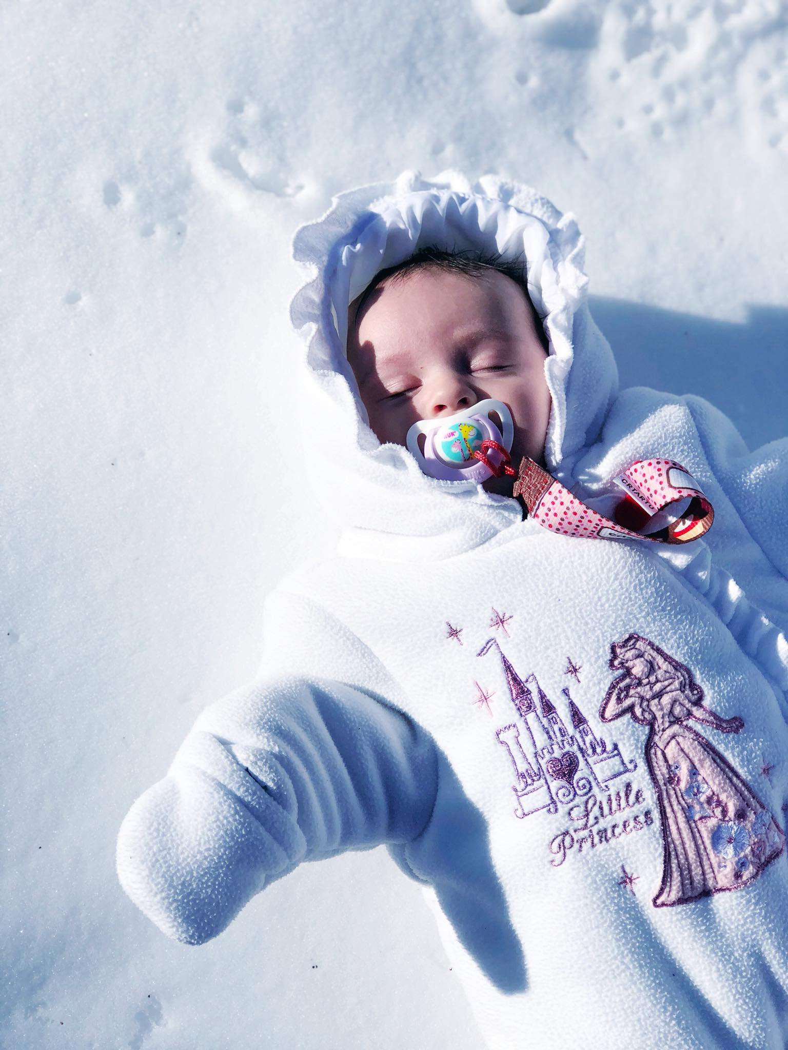 Baby girl laying in the snow wearing a white snowsuit with Sleeping Beauty on it