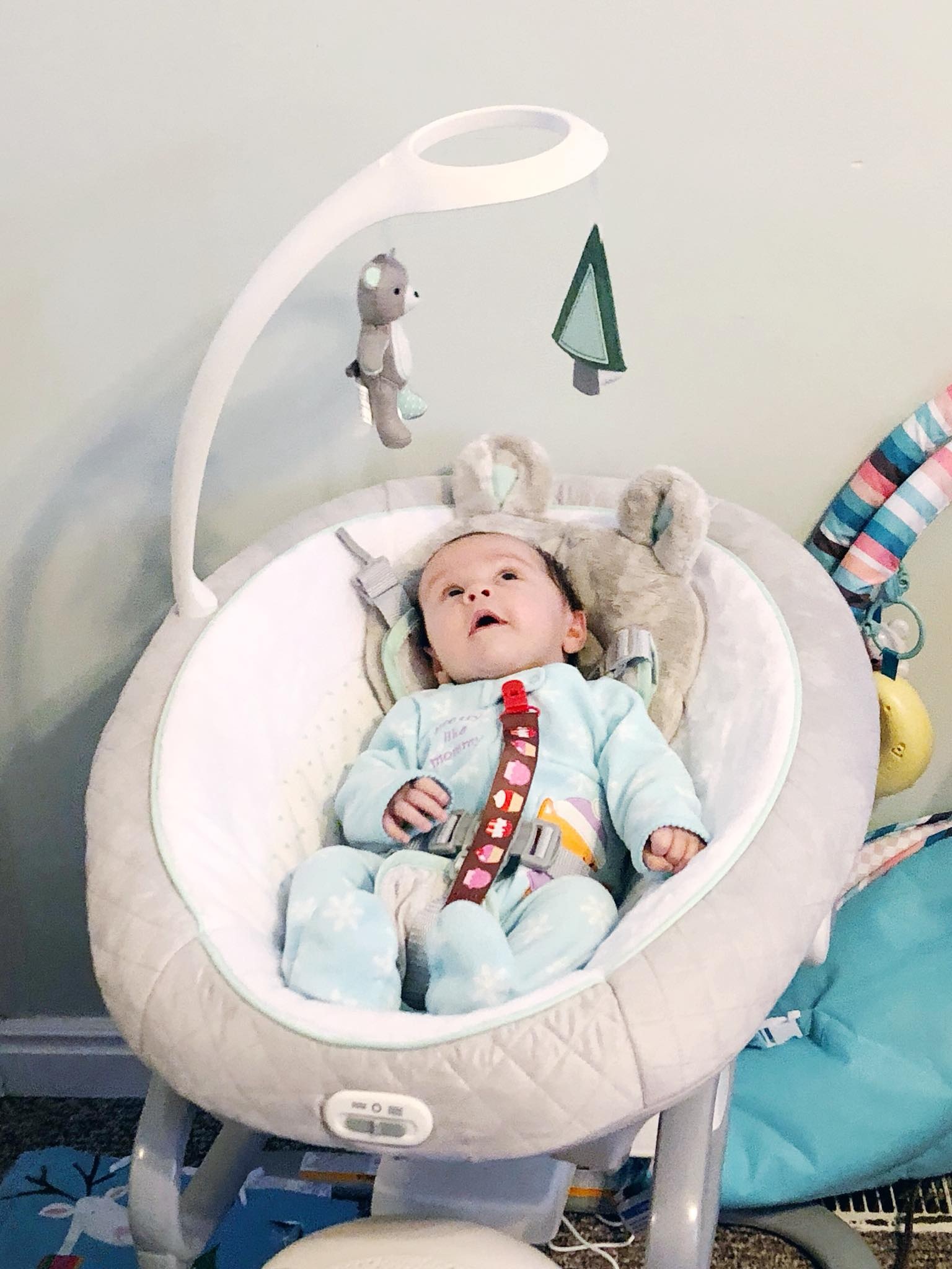 Baby girl admiring the toys hanging from her Graco Everyway Soother Baby Swing