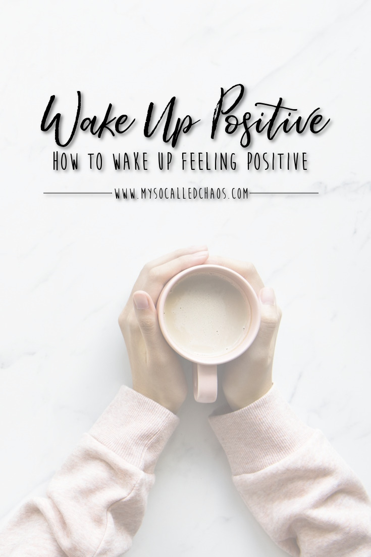 "Pinnable image for ""How To Wake Up Feeling Positive"" showing a woman holding her coffee."