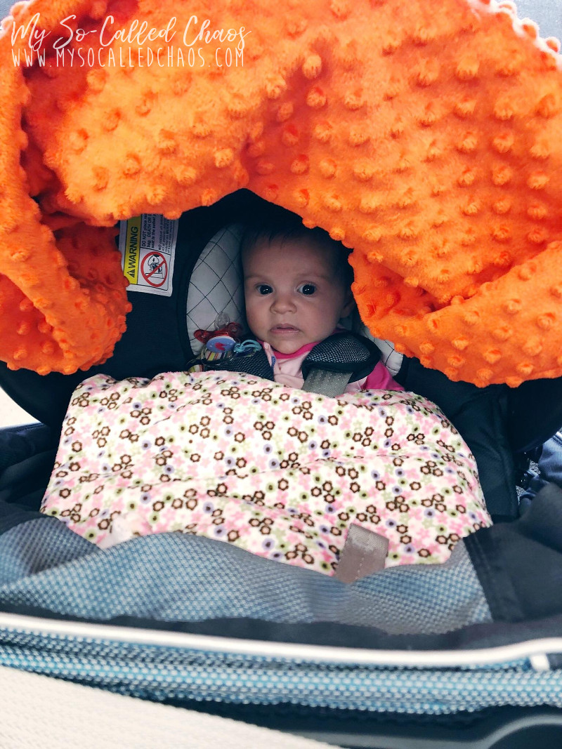 Baby Amélie at 3 months old, sitting in her Chicco carseat with a pink blanket and Wonder Woman Carseat Canopy.