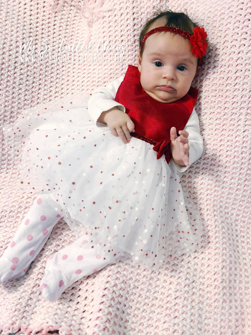 Baby girl laying on a pink crocheted blanket and wearing a red valentine's day party dress and flower