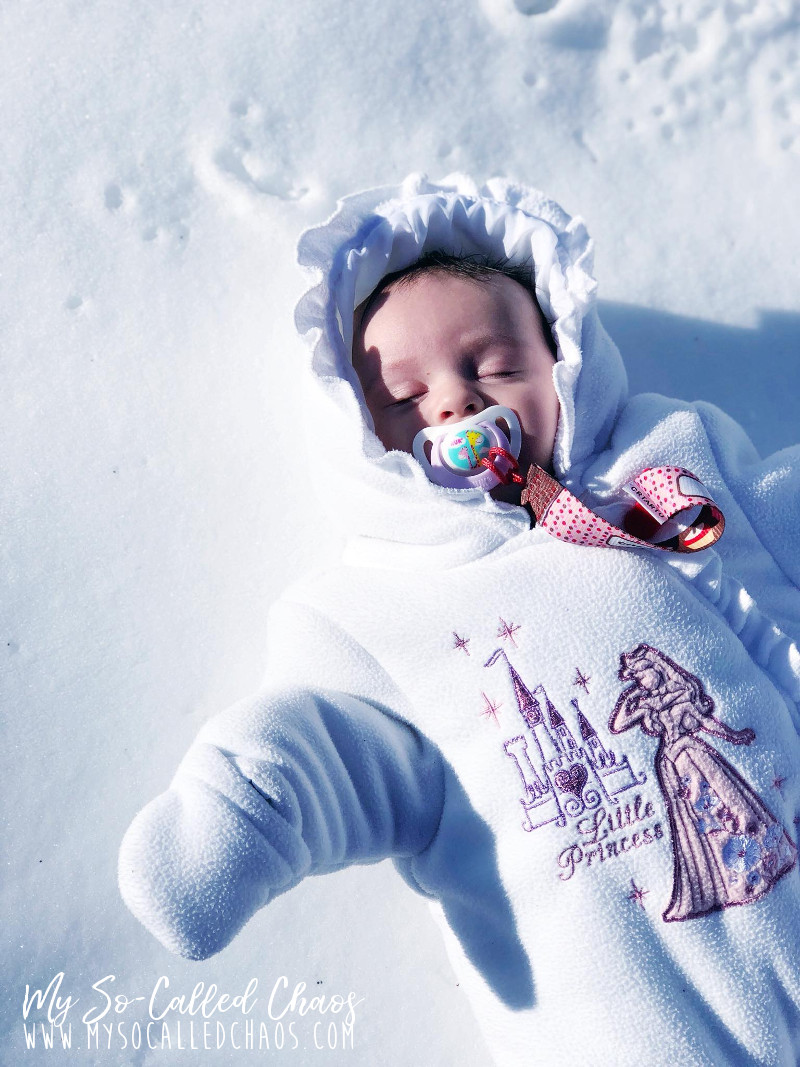 2-month-old baby in a white snow suit with Sleeping Beauty on it laying in the snow for the first time