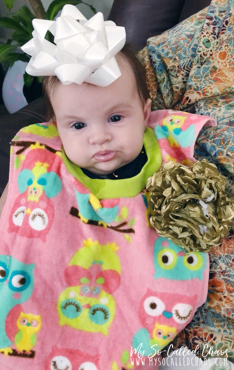 Baby Amélie at 3 months old wearing a bib, looking unimpressed, with giant gift bows stuck to her head and arm.
