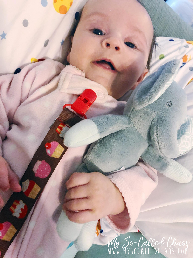 Amélie wearing pink footie jammies and looking happy while holding a small stuffed elephant her Aunt Cristina sent her.
