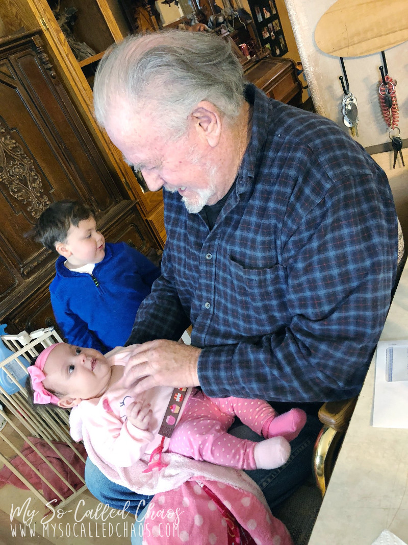 Grandpa Nick, a 70 year old man in a blue plaid shirt, holding baby Amelie at 3 months old and tickling her stomach. She's wearing pink heart pants, a kitty sweater, and a pink bow. Sam, a 4 year old boy with brown hair, lurking in the background in a blue sweater.