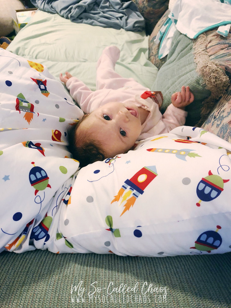 Baby Amélie at 2 months old, laying on a space-themed pillow on the couch and looking backwards at her momma.