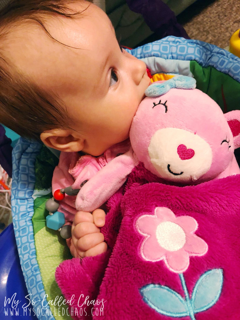 Baby girl sucking on her pink lovee bear