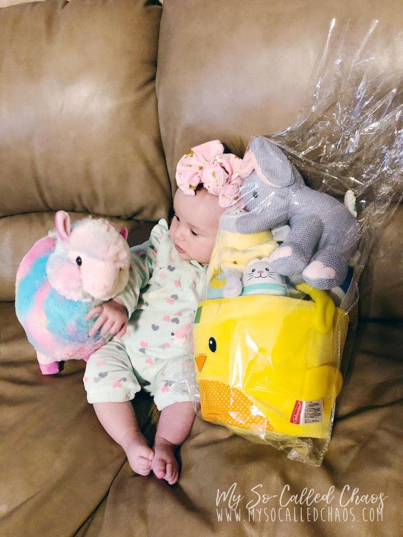 Baby girl sitting on the couch with her easter basket and a tie dye Easter llama stuffed animal.