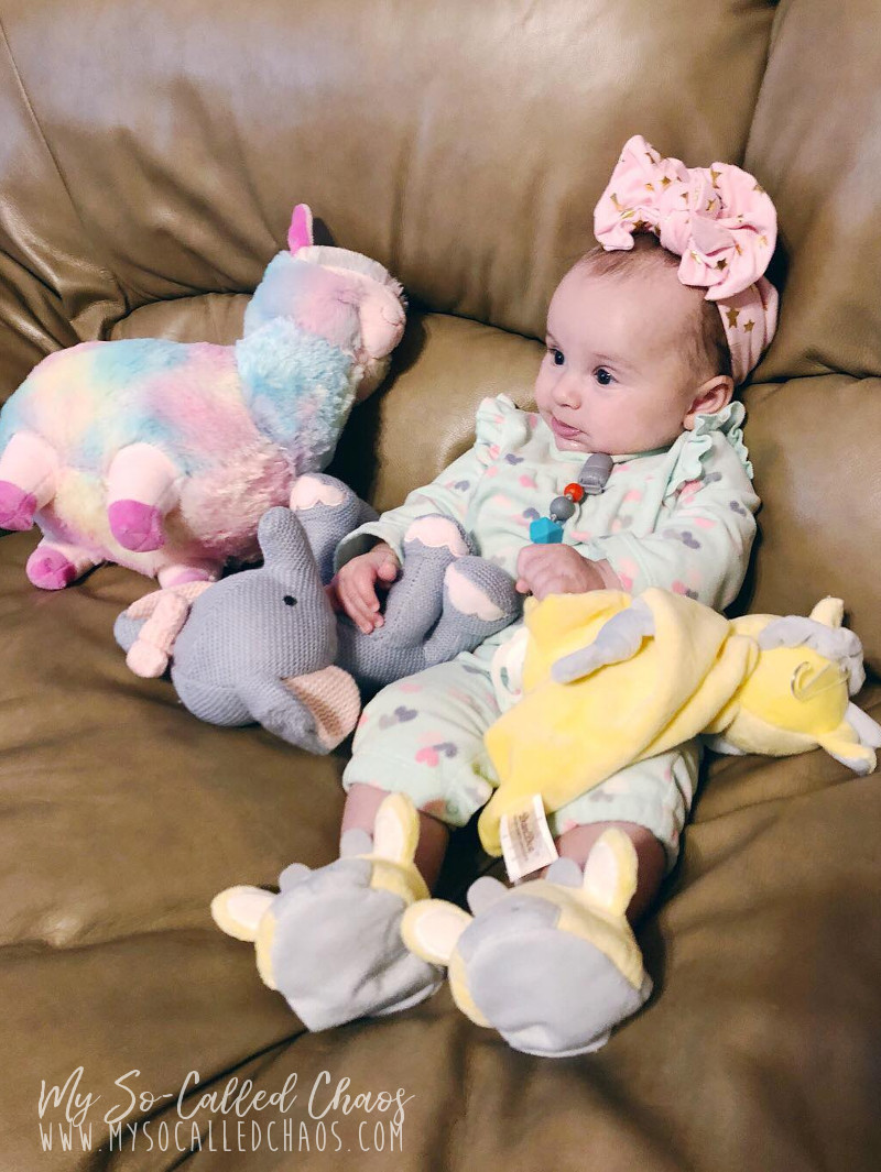 Baby girl sitting on the couch with her easter stuffed animals