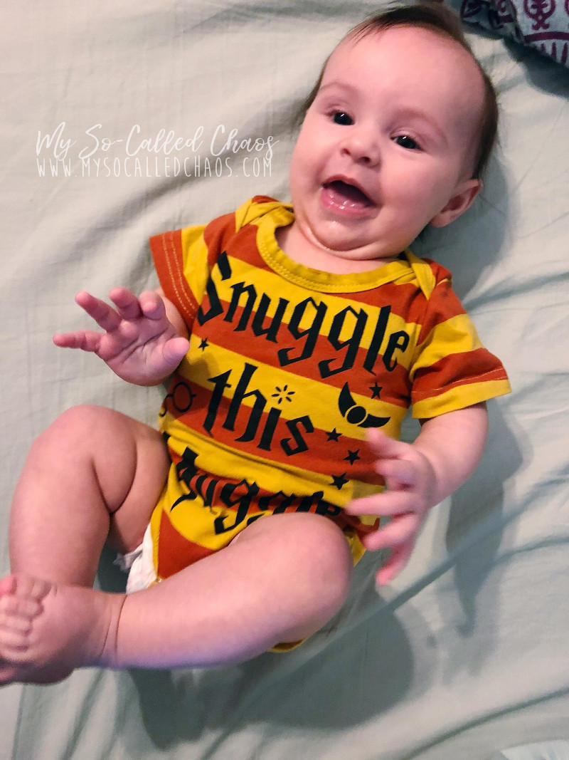 "Baby girl wearing a harry potter onesie that says ""Snuggle this Muggle"" and laughing"
