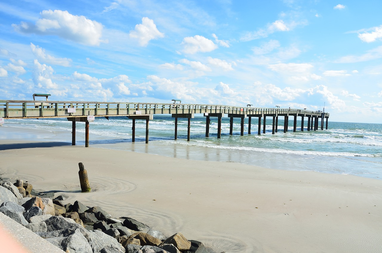 A long pier in St. Augustine Florida. Beach, blue skies, and lovely teal waters at low tide.