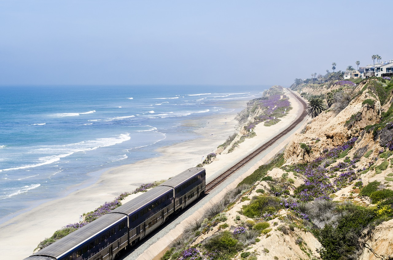 A train making it's way up the coast of California. Lovely dessert views to the right, and the vast Pacific Ocean to the left.