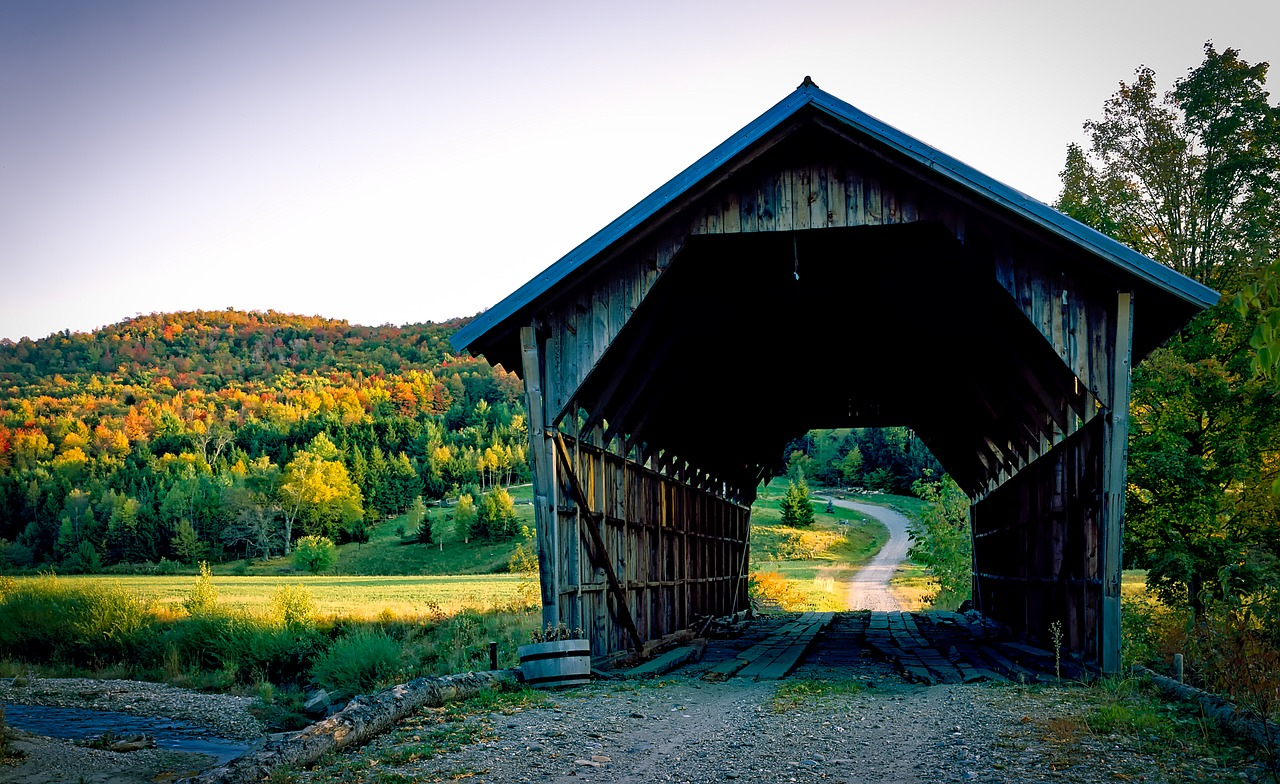 A wooden covered bridge over a rocky road as the leaves are changing in a Vermont Fall.