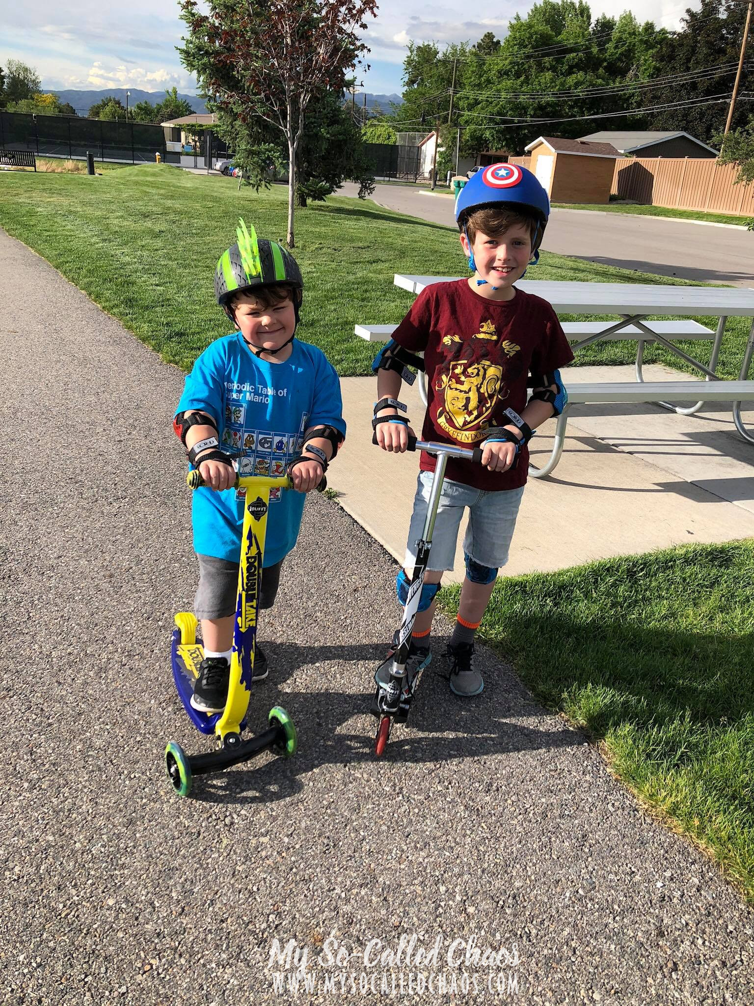 Two boys riding scooters at the park, wearing helmets and elbow/knee pads.
