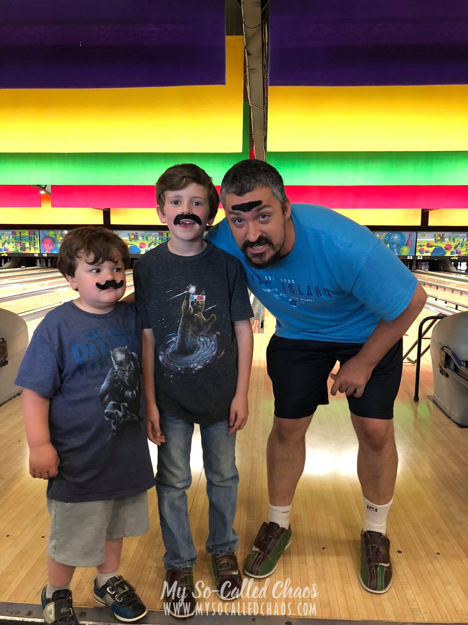 Man and two boys wearing fake mustaches at Fat Cats Bowling in Salt Lake City, UT