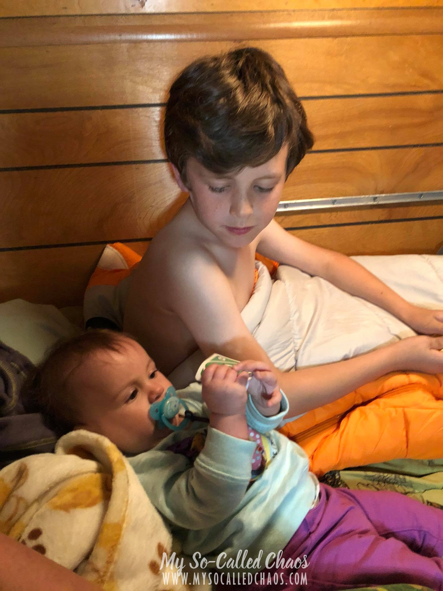 9 year old boy watches his 6 month old sister hold Uno cards.