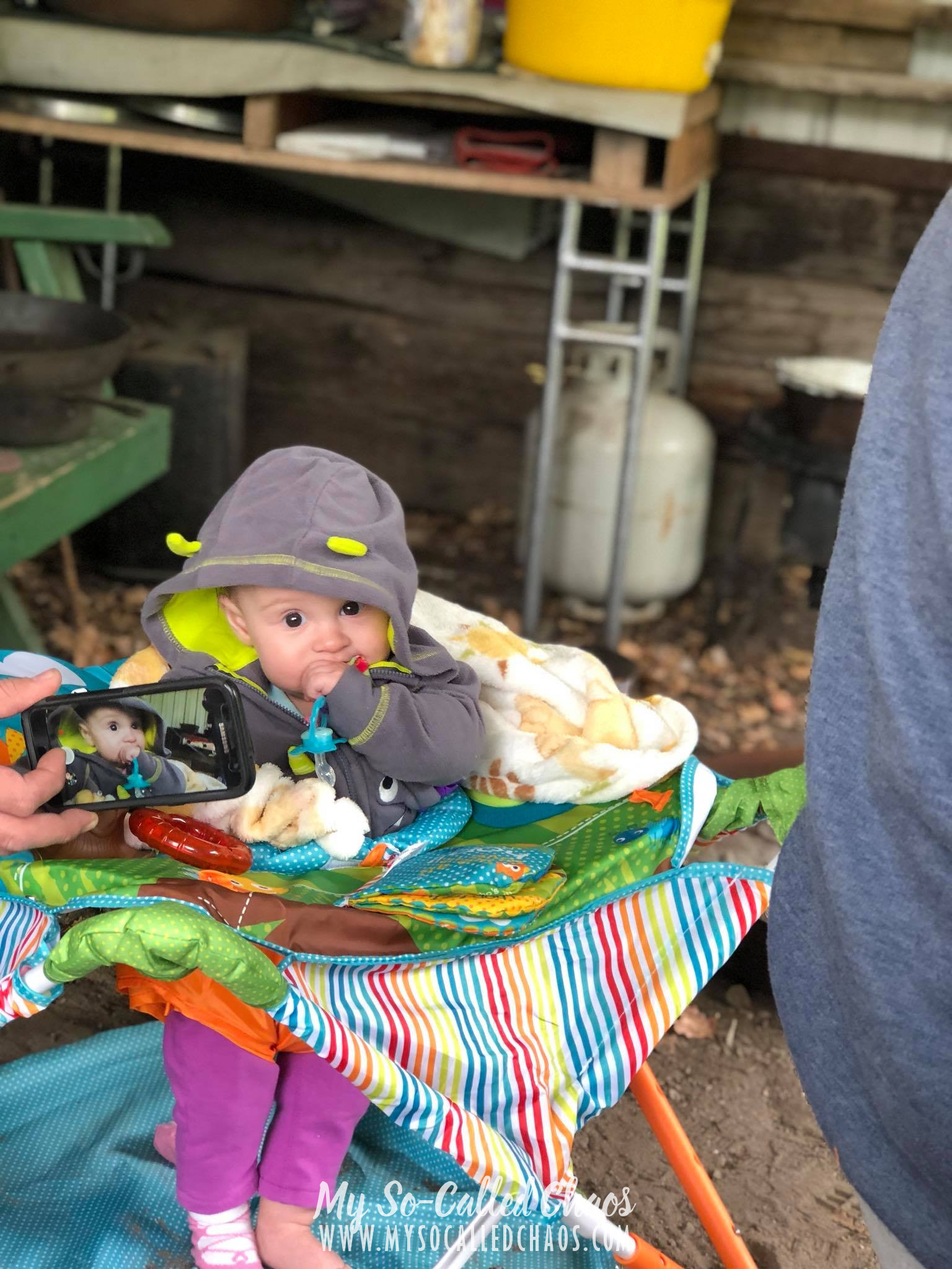 Baby girl bundled up and playing in her Summer Infant Portable Bouncer and Activity Center.