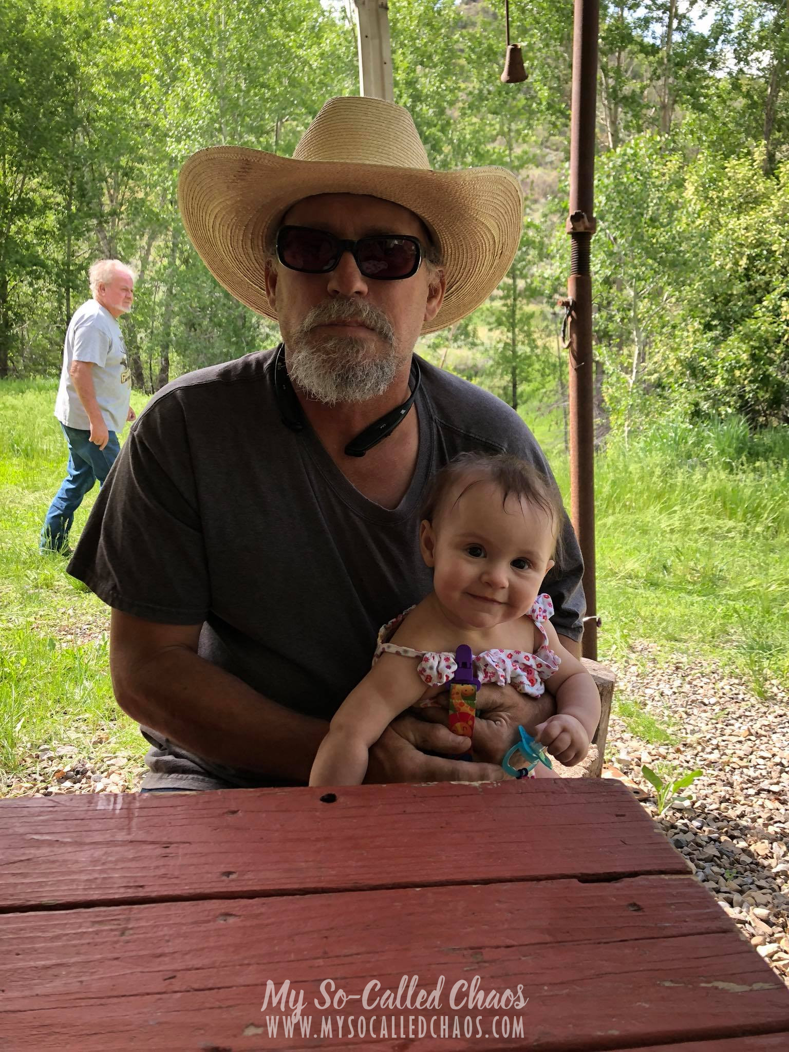 Man in a cowboy hat holding a baby girl in a Summer onesie and smiling at the camera.