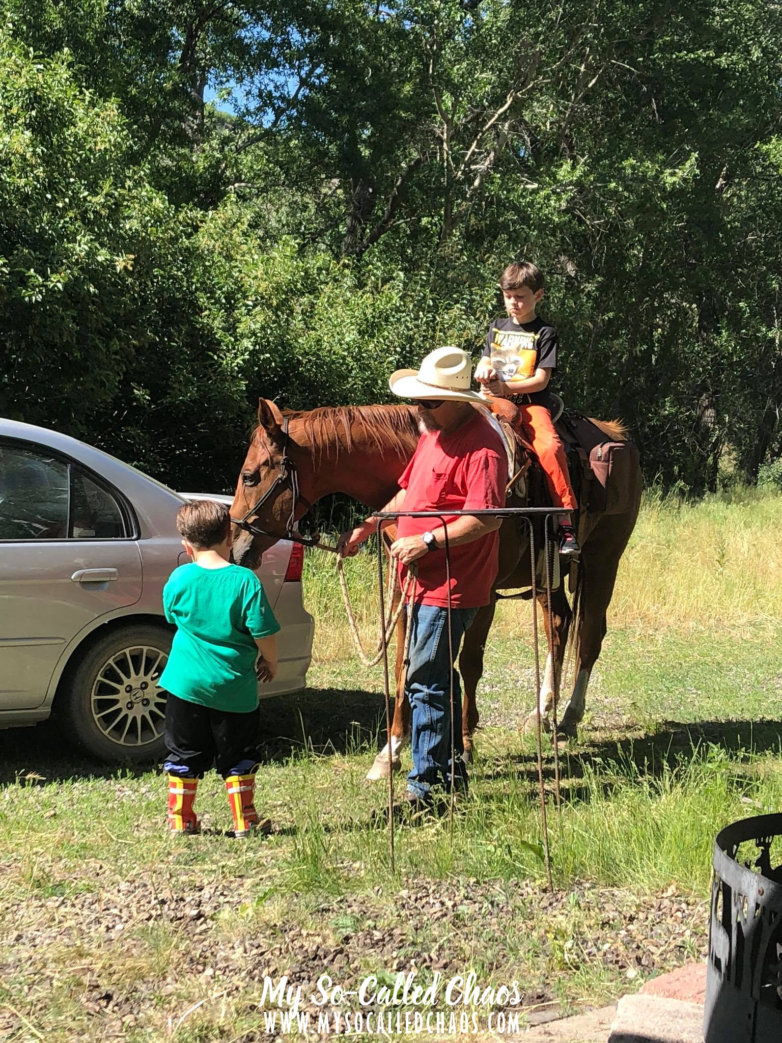 Man in a cowboy hat and red shirt leading a 9 year old boy in orange jeans around on a tall brown horse while a 5 year old boy in a green shirt pets the horse.