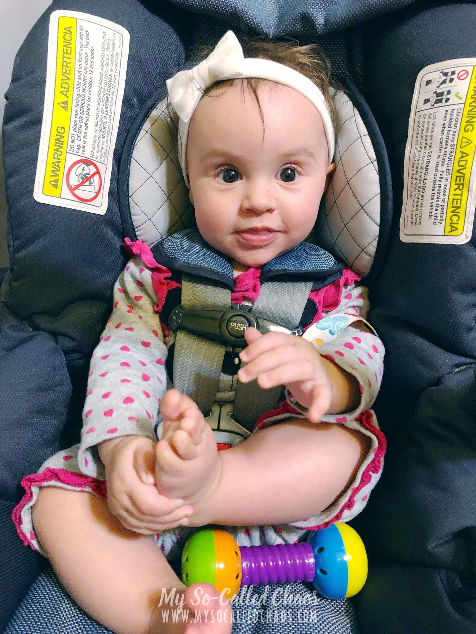 7 month old baby girl in her carseat playing with her feet.