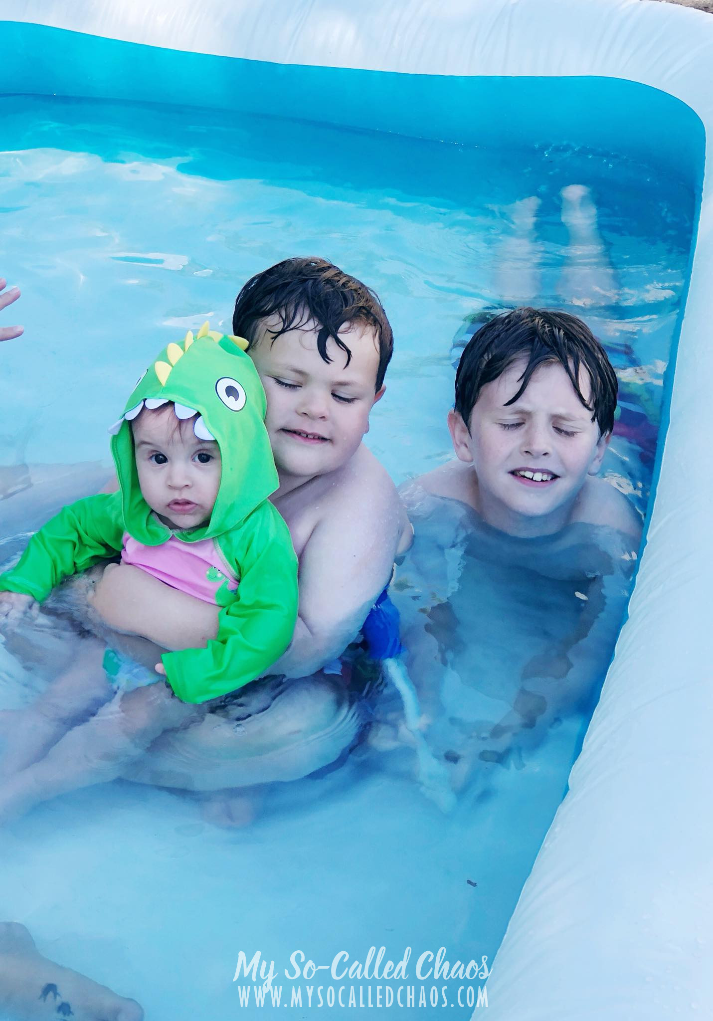 Two boys holding their baby sister in a dinosaur swimsuit and rashguard while swimming in a blow up pool.