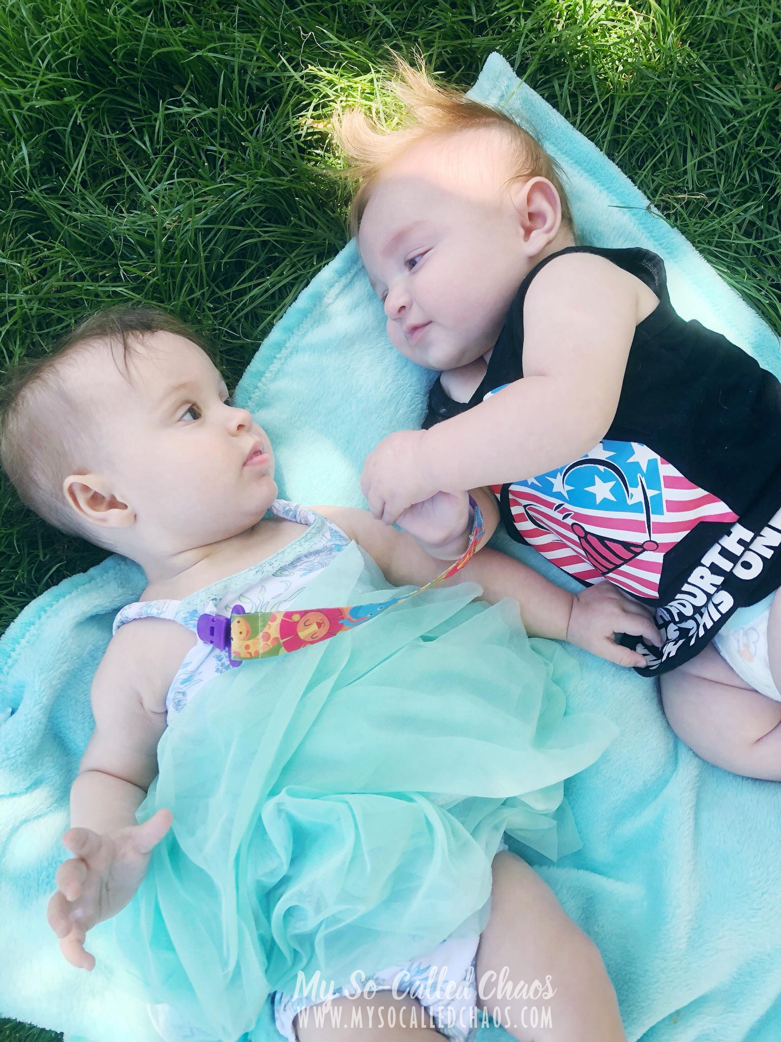 6 month old baby girl in a seafoam dress laying on a blanket next to a cute little 4 month old boy in a Darth Vader shirt and diaper.