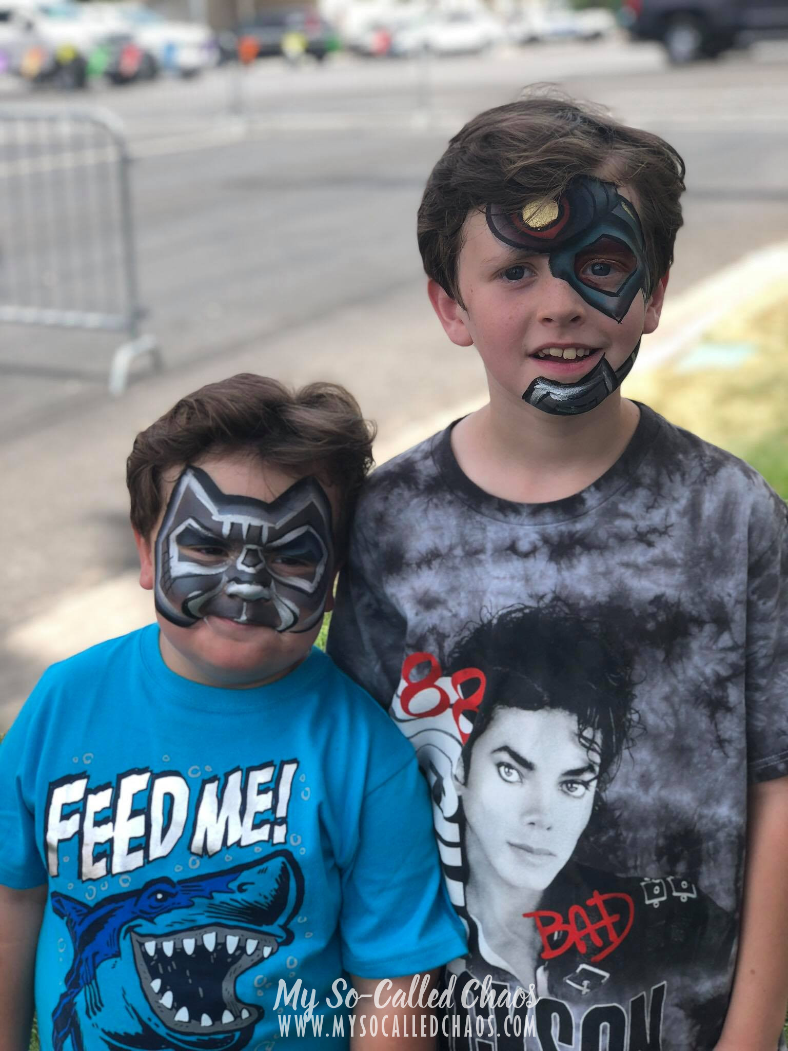 5 year old boy in a blue shirt with a Shark that says Feed Me! with his face painted like Black Panther standing next to a 9 year old boy wearing a Michael Jackson T-shirt who's face is painted like Cyborg.