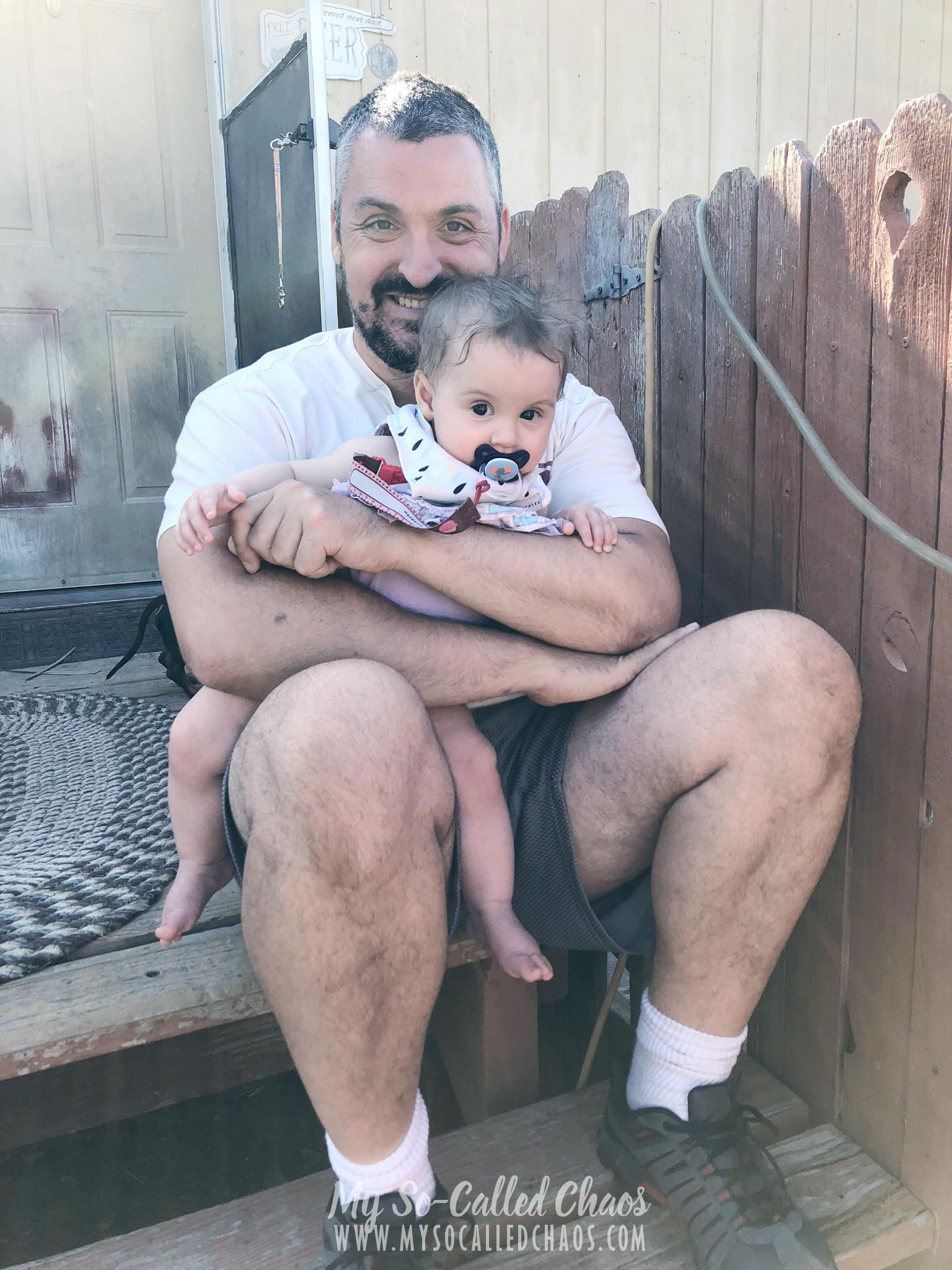 7 month old baby girl with a pacifyer being held by her dad on the porch.