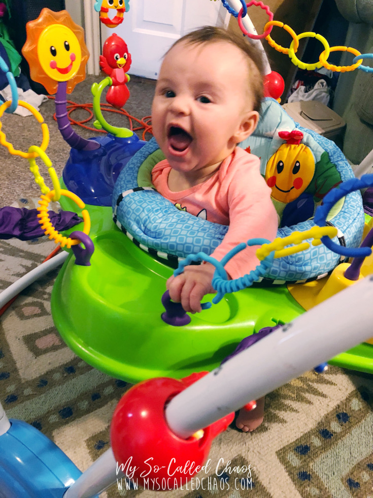 Baby girl laughing excitedly as she bounces in her Baby Einsteins Neighboorhood Friends Bouncer