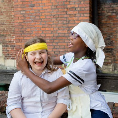 Little girl wearing a Mary Seacole Nurse Costume and playing nurse with a friend - handmade dress up kit via Etsy