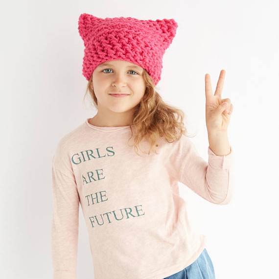 "Kids Pink Pussy Cat Hat and a girl wearing a shirt saying ""Girls are the future"""