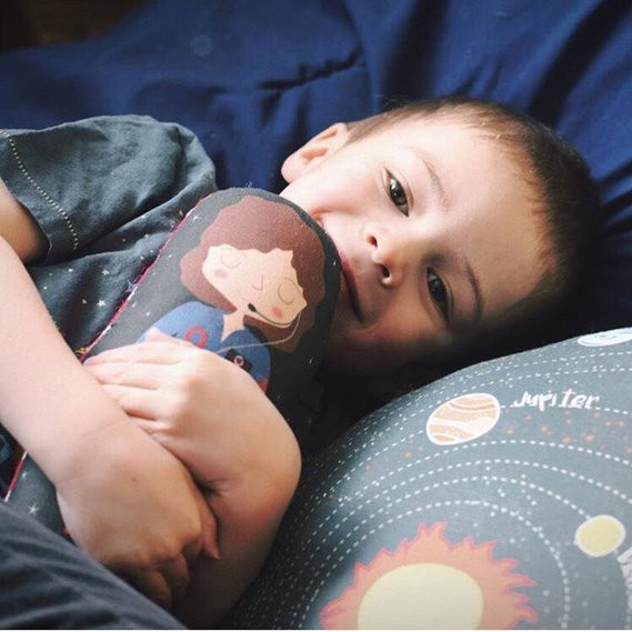 Boy cuddling a handmade Sally Ride Feminist Plush Doll