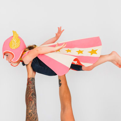 Girl wearing a handmade pink superhero costume from Etsy and pretending to fly