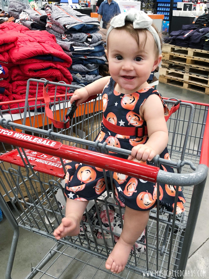 10 month old baby girl wearing the cutest little pumpkin dress we bought on Wish, and sitting in a shopping cart at Costco.