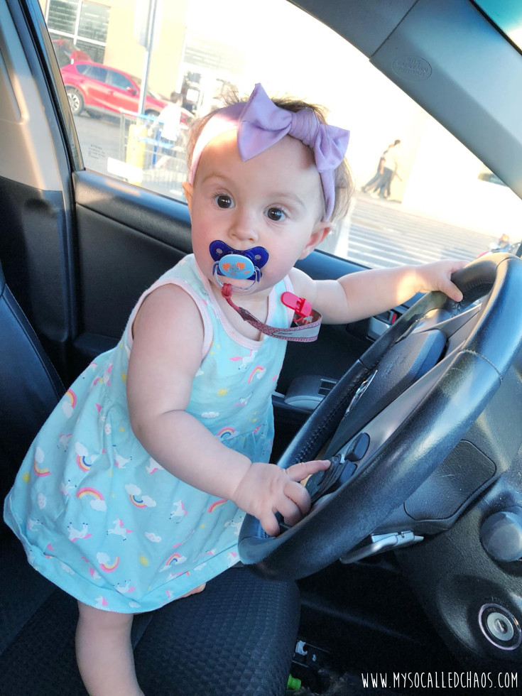 9 Month old baby girl in a dress and headband pretending to drive the car.