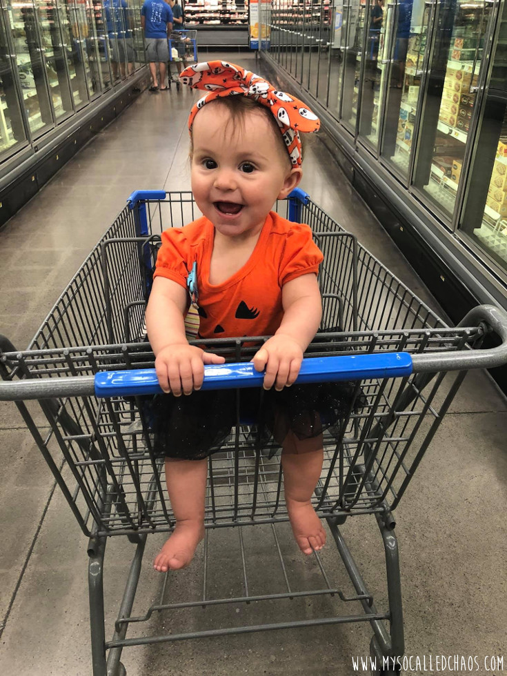 9 month old baby girl wearing a Jack O'Lantern Dress and Halloween headband sitting in a cart at Walmart.