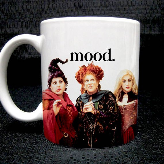 "An adorable Halloween mug that says ""mood"" on it with an image of the Sanderson Sisters looking shocked."