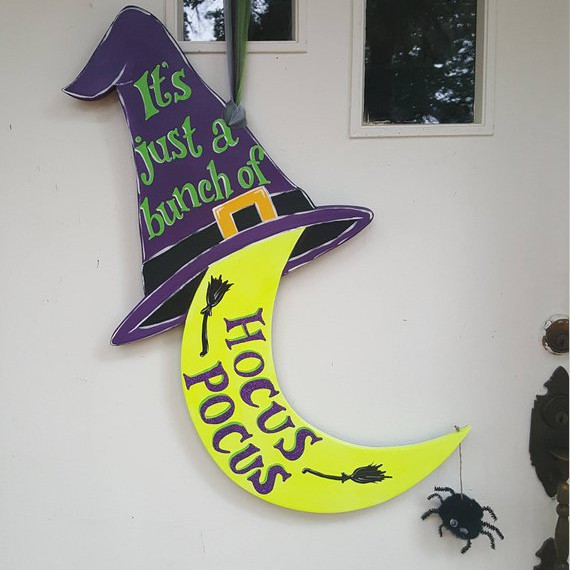 Door hanger featuring a glow in the dark moon with a witch hat saying