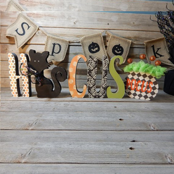 Adorable wooden Hocus Pocus inspired letters, the first word spells out Hocus with a black cat for the O and Pocus is on a cauldron at the end.
