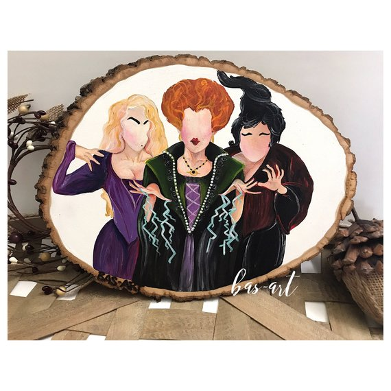 A wooden slice painted with faceless Sanderson Sisters from Hocus Pocus. Art by Bas Art