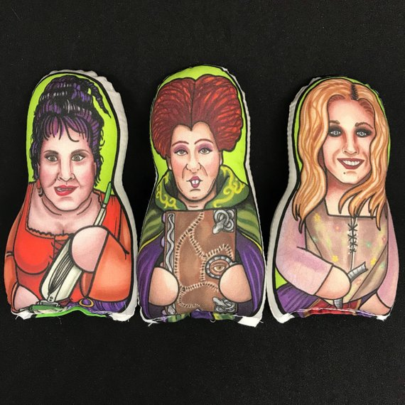 Plush pillows featuring painted images of the Sanderson Sisters from Hocus Pocus. Art by The Cuddle Cult