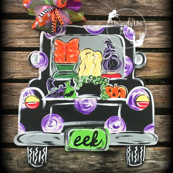"A wooden door hanger featuring a a back view of a truck with the Sanderson sisters inside and a license plate that says ""eek"". Art by Uniquely Urs Decor"