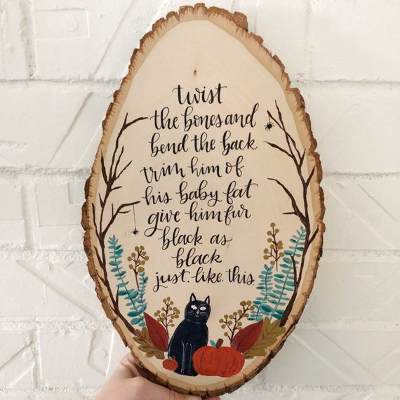 Hocus Pocus Wood Round art featuring Binx the Cat and the words to the Twist the Bones spell that the Sanderson Sisters use to change him from boy to cat. From the shop Helmies.