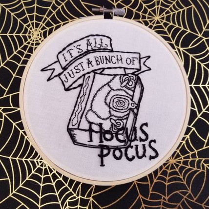 An emboridery hoop art inspired by Hocus Pocus and showing the Book and the words