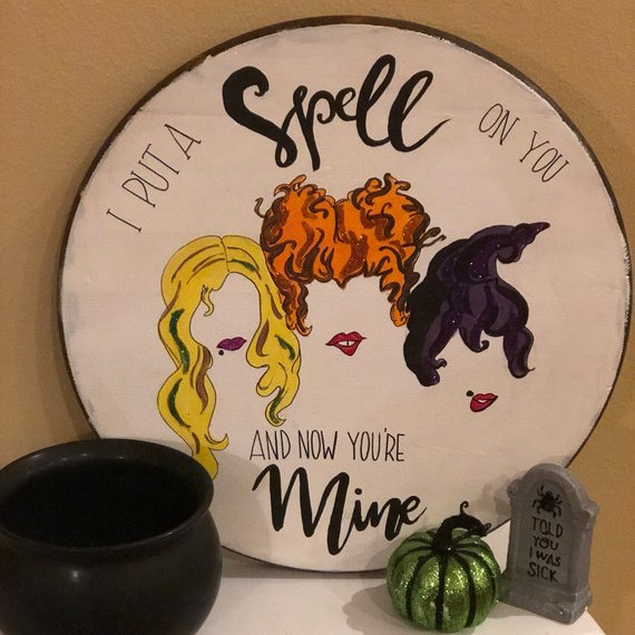 "Round wooden door hanger saying ""I put a spell on you and now your mine"" and featuring the hair and lips of each Sanderson Sister from Hocus Pocus. Art by Ophelia Lane Designs"