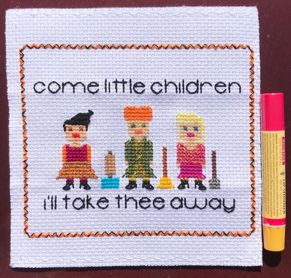 "A Hocus Pocus inspired cross stitch art showing the three Sanderson Sisters, their flying contraption, and the words ""Come little children I'll take thee away"" by The Nerdy Needlepoint"