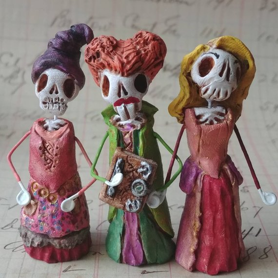 Amazing day of the dead Hocus Pocus inspired figurines showing off the Sanderson Sisters like they'd be for Dia de los Muertos. Art by Dalaimomma
