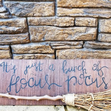 "Sign featuring an actual twig broom and the words ""It's Just a Bunch of Hocus Pocus"". Art by Ali's Rustic Lounge"