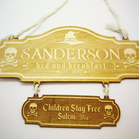 "Wooden sign saying ""Sanderson Bed and Breakfast"" with skulls and cross bones, and another sign saying ""Children Stay Free, Salem MA"""